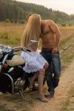 Un jeune couple dans l'amour sur une moto dans le domaine Images stock