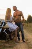 Un jeune couple dans l'amour sur une moto dans le domaine Photo stock