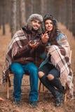 Un jeune couple dans la forêt, thé potable, le type indique avec son doigt la distance outdoors Photographie stock