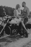 Un jeune couple dans le domaine à côté de la moto Photo stock