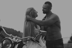 Un jeune couple dans le domaine à côté de la moto Photographie stock libre de droits