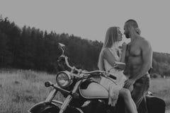 Un jeune couple dans le domaine à côté de la moto Images libres de droits