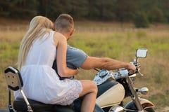Un jeune couple dans le domaine à côté de la moto Image stock