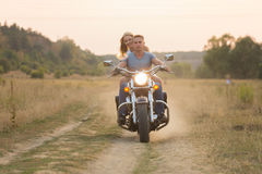 Un jeune couple dans le domaine à côté de la moto Image libre de droits
