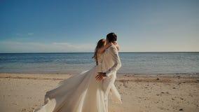 Un jeune couple des nouveaux mariés courant pour se rencontrer dans la perspective de la mer Une photo tropicale banque de vidéos