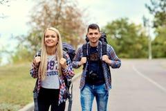 Un jeune couple des randonneurs de touristes dans une hausse sur la route Images libres de droits