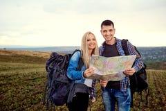Un jeune couple des touristes avec une carte dans une hausse en nature Image stock