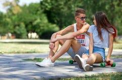 Un jeune couple doux de chute-dans-amour se reposant au sol sur un fond brouillé de parc Relations et concept d'amour Images stock