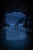 Un jeune couple embrassant à une entrée de caverne par la mer Images libres de droits