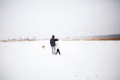 Un jeune couple enceinte marchant dans les bois avec le chien de traîneau rouge de chien Photos stock