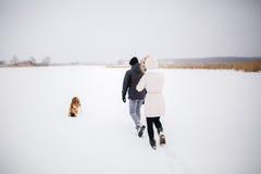 Un jeune couple enceinte marchant dans les bois avec le chien de traîneau rouge de chien Photographie stock libre de droits