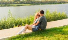 Un jeune couple est romantique en parc sur un lac L'homme et la femme s'asseyent dans le soleil d'été dans l'herbe verte Photo stock