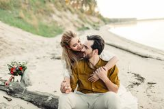 Un jeune couple est souriant et étreignant sur la plage Cérémonie de mariage rustique dehors La mariée et le marié regardent l'un Images libres de droits