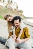Un jeune couple a l'amusement et étreint sur la plage La belle fille embrassent son ami de dos mariage dessin-modèle Images stock