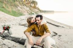 Un jeune couple a l'amusement et étreint sur la plage La belle fille embrassent son ami de dos Promenade Wedding a Images stock