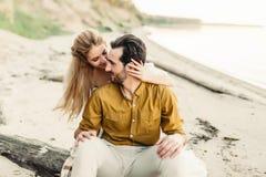 Un jeune couple a l'amusement et étreint sur la plage La belle fille embrassent son ami de dos Promenade Wedding a Photos stock