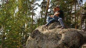 Un jeune couple marche dans une forêt de pin sur les roches en pierre un jour ensoleillé lumineux banque de vidéos