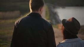 Un jeune couple marche en parc automnal tenant des mains et souriant affectueusement Tir moyen blanc d'isolement de vue arrière banque de vidéos