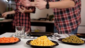 Un jeune couple met la table, se préparant au dîner Plats, jus, nourriture banque de vidéos