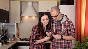 Un jeune couple met la table, se préparant au dîner Plats, jus, nourriture Parler au téléphone dans la cuisine banque de vidéos