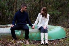 Un jeune couple mignon se reposant sur un vieux bateau Images libres de droits