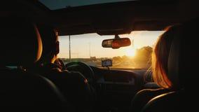 Un jeune couple multi-ethnique conduit à la voiture dans un coucher du soleil La lumière illumine admirablement les cheveux du `  Images libres de droits