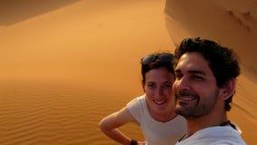 Un jeune couple prenant un individu décrit tout en s'élevant jusqu'au dessus de la grande dune de sable en mer dunaire rouge d'er Photo libre de droits