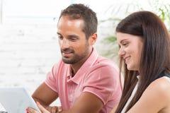 Un jeune couple regardant un comprimé Images libres de droits