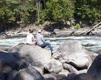 Un jeune couple se reposant sur des roches Photos stock