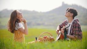 Un jeune couple se reposant sur un pré vert clair et ayant le pique-nique - un homme jouant la guitare tandis que son amie heureu banque de vidéos