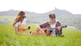 Un jeune couple se reposant sur un pré vert clair - un homme jouant la guitare tandis que son vin de versement d'amie dans les ve banque de vidéos