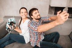 Un jeune couple se repose sur le divan et fait le selfie avec un robot Photo stock
