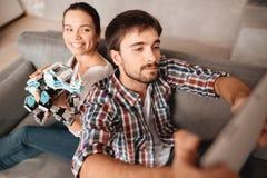 Un jeune couple se repose sur le divan et fait le selfie avec un robot Images stock