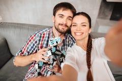 Un jeune couple se repose sur le divan et fait le selfie avec un robot Image stock
