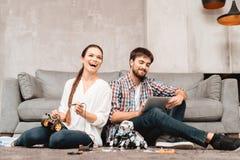 Un jeune couple se repose sur le plancher dans le salon Ils rassemblent des robots Photo stock