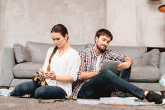 Un jeune couple se repose sur le plancher dans le salon Ils rassemblent des robots Images stock