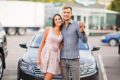 Un jeune couple se tient près de leur nouvelle voiture d'occasion images libres de droits