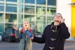 Un jeune couple se tient sur la rue et crier par derrière un smartphone cassé Photos stock