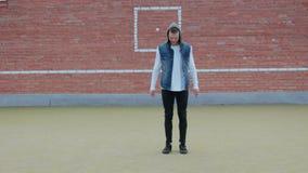 Un jeune danseur masculin caucasien, l'acrobate dans le pantalon noir et le gilet bleu de denim avec le capot, ex?cute une s?ance banque de vidéos
