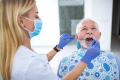 Un jeune dentiste féminin commande la santé de la dent images libres de droits