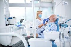 Un jeune dentiste féminin commande la santé de la dent photos libres de droits