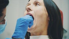 Un jeune docteur est une femme habillée dans des vêtements blancs médicaux et un masque, fait un examen patient Au cours de l'exa banque de vidéos