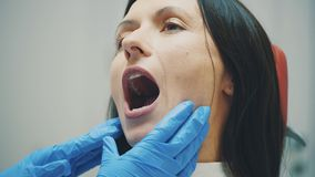 Un jeune docteur est une femme habillée dans des vêtements blancs médicaux et un masque, fait un examen patient Au cours de l'exa clips vidéos