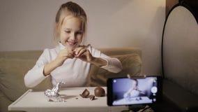 Un jeune, drôle blogger de fille note la question L'enfant déballe l'oeuf avec une surprise clips vidéos