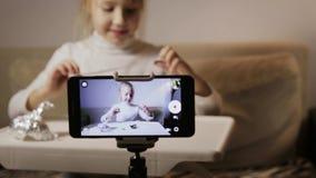 Un jeune, drôle blogger de fille note la question L'enfant déballe l'oeuf avec une surprise banque de vidéos