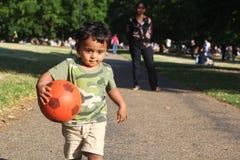 Un jeune enfant en bas âge indien courant avec la boule rouge Image stock