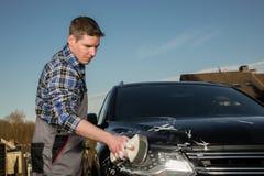 Un jeune est cleanig sa voiture sur la rue Images stock