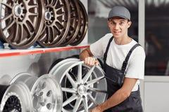 Un jeune et attirant mécanicien de voiture choisit une jante de pneu photos libres de droits
