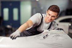 Un jeune et qulified mécanicien de voiture fixe une voiture à un service de voiture et de véhicule photos stock