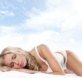 Un jeune et sexy blond dort sur la soie Images stock
